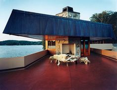 Deck furniture made from millennia-old hand-carved mahogany tree stumps.- Massaro House /  Petra Island, New York / 2003-2007 / Usonian / Thomas Heinz -- The cantilevered 78 foot long wing reaches out across the lake, soaring over a single column towards the water. The original plan included stairs reaching far down on the water surface but modern building regulations meant this feature had to be omitted. The result looks very much Wrightian but also has modern touches that make it unique.