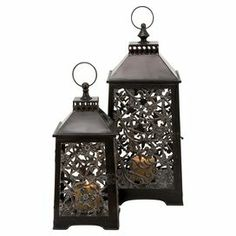 "Set of 2 metal candle lanterns with scrolling floral details.  Product: Small and large lanternConstruction Material: MetalColor: Antique brassAccommodates: (1) Candle - not includedDimensions: Small: 16"" H x 8"" W x 8"" DLarge: 22"" H x 10"" W x 10"" D"