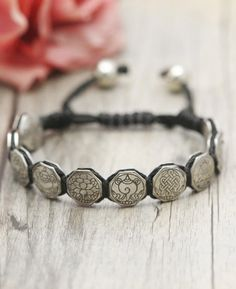 f30c9300c9 Bracelet of interweaving black cord is fitted with metal discs engraved with  one of the eight auspicious symbols of Tibetan Buddhism.