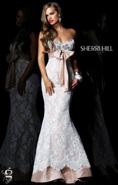 Sherri Hill has done it again! She has perfectly designed a dress that can be worn to so many events. Whether it's your prom, pageant, gala, or even your WEDDING, Sherri Hill 21017 has got to be your choice! This mermaid inspired silhouette is sexy and elegant, especially because of the ivory lace that lays over the nude fabric. The same nude fabric is brought up to the top with an oversized bow at the waist. Pearl and diamonds adorn the sweetheart top and add a classy element that makes…