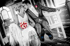 Striking black and white photo of a couple at Disney's Wedding Pavilion with pops of color #Disney #WeddingPavilion #kiss