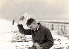 Winter shots at the beach strip. This image shows a man combing his hair with an ice comb.