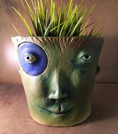 This one of a kind sculpture designed to be a stand out in your garden or in your home. He is made of high fire clay and fired to 2200 degrees. There is a hole in the top and you can plant anything you like in him. I think these pieces look great with succulents, cat grass or anything that grows to look like hair. This piece is approximately 8 wide, 7 tall and has lots of detail. This planter is is glazed in matte glaze with various accents. It also has a drain hole in the bottom.