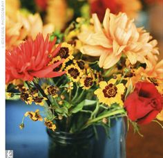 A blend of yellow, orange, and red ranunculuses, freesias, dahlias, roses, and lilies sat at the center of each table at Dede and Adam's reception.