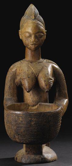 África:, Yoruba (Nigeria).  Rodillas Mujer sosteniendo un plato, con un niño onher espalda.  Madera, restos de pigmento rojo camwood.  Altura: 16 ½ ...