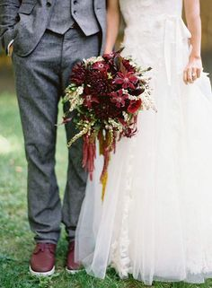 Groom in a grey suit with burgundy shoes and the bride carrying a burgundy bouquet @myweddingdotcom