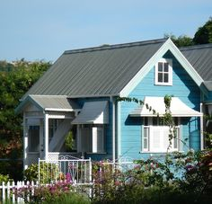 House from Barbados in light blue and white with Caribbean architecture, designed to protect from the regional weather.