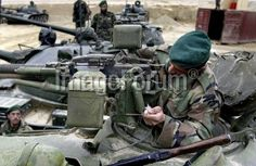 An Afghan national army soldier (R) checks a Russian-made T-55A type tank seized from regional factional commanders during a campaign on collecting heavy weapons in the northern city of Mazar-i-Sharif, 02 December 2003.