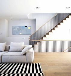 Living room with grey couch and a striped black and white rug