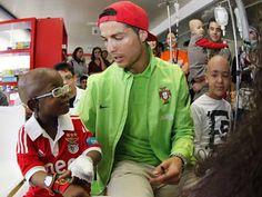 Manuel, um menino benfiquista, ao lado de um jogador de futebol português...