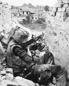 From an elevated position behind a shattered wall, a U.S. Marine machine gunner, keeps his weapon ready as he looks for enemy forces along a canal in Hue City, February 14, 1968.