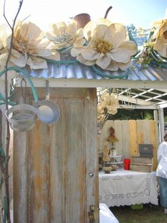 Market booth, tin roof, large paper flowers, green garden hose, old door.