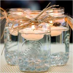 Mason Jars and Candles Keep it simple and use floating candles as your centerpiece. They'll glisten in clear Mason jars. Mason Jars and Candles Keep it simple and use floating… Deco Champetre, Do It Yourself Wedding, Mason Jar Centerpieces, Simple Centerpieces, Easy Table Decorations, Country Wedding Centerpieces, Wedding Centerpieces Mason Jars, Ceremony Decorations, Mason Jar Thanksgiving Centerpieces