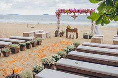Cerimônia colorida na praia com bancos de madeira e arco de flores. Foto: Jeff e Gal