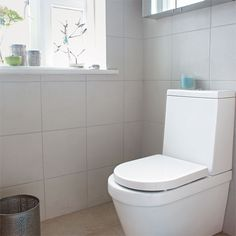 En-suite bathroom with white tiles and white toilet