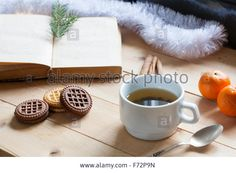 Download this stock image: Cup of hot tea with books, cookies and tangerines on light wooden table - F72P9N from Alamy's library of millions of high resolution stock photos, illustrations and vectors.