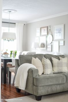 An open-concept dining room and living room is bright and inviting with a large farmhouse table, grey couch and eclectic gallery wall   A Burst of Beautiful