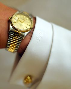 Tiffany & Co. gold knot cufflinks, a Rolex watch, and a shirt with monogrammed cuffs