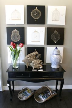 Arrimo de madera negro, set de 9 cuadros solitarios petit, canastos revisteros, pescados de madera reciclada decorativos, florero de vidrio y base de cerámica.   Tienda Bandara Home & Deco