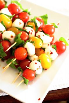 Caprese Skewers - 1 pint cherry tomatoes    1 pint yellow tomatoes    1 pound fresh ciliegine or other type of mozzarella cheese, fresh    1 cup fresh basil leaves, gently torn into 1/2-inch pieces    Pinch red pepper flakes, to taste    Sea salt, to taste    Extra-virgin olive oil, for drizzling    Wooden skewers, for serving
