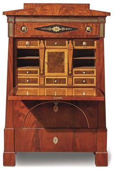 Empiresekretär Um 1820/25 Trapezförmiger Korpus auf Würfelfüßen, die Front gegliedert in geometrische Delder und Giebel als oberer Abschluss, die Inneneinrichtung aus Schüben und Tabernakelfach. Mahagoni und andere heimische und überseeische Laubhölzer furniert, teilebonisiert und mit geometrischen Messingbändern eingelegt, vergoldete Messingbeschläge. 160 x 106 x 52 cm.
