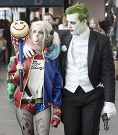 a woman dressed as harley quinn walks alongside a man dressed like the joker in suicide - The Joker And Harley Quinn Halloween Costumes