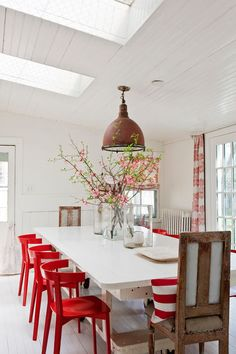 Modern country #dining room with #red chairs and white floors. Love that pendant!