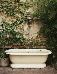 Clawfoot tub - outdoor shower mix. I'd climb some fragrant honeysuckle or jasmine or orange on that wall!