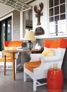 coastal decor in orange. I love the painted wicker chairs.