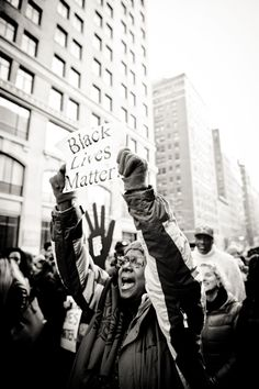 """A demonstrator holds up a makeshift """"Black Lives Matter"""" sign as she chants with the crowd of thousands slowly moving through the streets of downtown Manhattan. Dec. 14, 2014"""