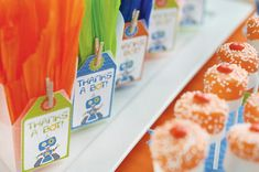 Marshmallow pops dipped in orange colored chocolate with sprinkles.