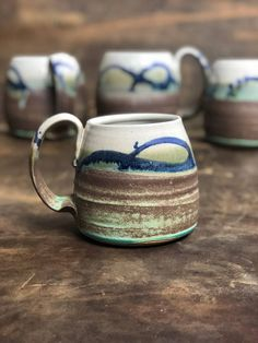 Handmade wheel thrown pottery mug in an earthy combination of a matte green and brown glaze with blue brushwork. Stoneware coffee mug cup. Functional pottery.