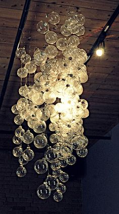 "DIY ""bubble"" chandelier (clear Christmas ornaments on string)  I might try putting them around an old lamp shade hoop, or maybe paint a quilters hoop...?"