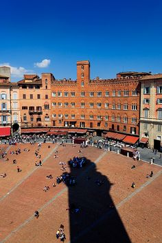 The Torre del Mangia casts its shadow onto Piazza del Campo, Siena, Italy
