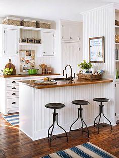 White kitchen, butcher block, wood floors, barstools