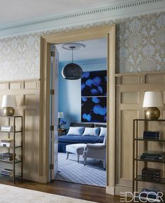 Vintage étagères by Jacques Adnet flank the doorway to the study, which has walls in Benjamin Moore's Blue Jean; the chair and ottoman are covered in a Pindler fabric, the pendant light is by Crate & Barrel, the carpeting is by Beauvais Carpets, and the photographs are by Renato Freitas.