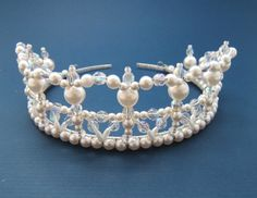 measures 1 1/2 inches high and was created using 4mm 6mm and 10mm white glass beads, 6mm crystals AB and attached to a silver toned tiara band.