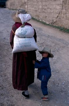 Mother and child walking through the streets in Kham province, Tibet, 1999 - Steve McCurry We Are The World, People Of The World, Tibet, Steve Mccurry Photos, Vivre A New York, World Press Photo, Expo Milano 2015, Afghan Girl, Picture Stand