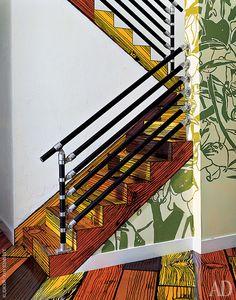 """На второй этаж ведет узкая лестница с металлическими перилами. Ступени, как и все полы в доме, из фанеры, на поверхности которой """"нарисованы"""" доски."""