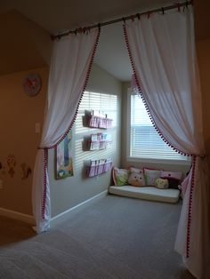 Dormer window area turned into cozy reading nook with curtains, book slings, and repurposed crib mattress.  Used closet rod & end caps to provide stability to rod (and cheaper than most curtain rods!).  Upcycled old crib sheets into coordinating pillows and book slings.  The three little girls love their new space!