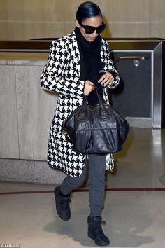 Mile-high style: She paired her statement coat with gray sweatpants, a black scarf and bla...