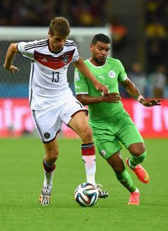 El Arbi Hillel Soudani Photos - Thomas Mueller of Germany and El Arbi Hillel Soudani of Algeria compete for the ball during the 2014 FIFA World Cup Brazil Round of 16 match between Germany and Algeria at Estadio Beira-Rio on June 30, 2014 in Porto Alegre, Brazil. - Germany v Algeria