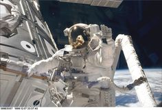 STS088-E-5057 (12-07-98) --- Astronaut James H. Newman, waves at camera as he holds onto one of the hand rails on the Unity connecting module during the early stages of a 7-hour, 21-minute spacewalk. Astronauts Newman and Jerry L. Ross, both mission specialists, went on to mate 40 cables and connectors running 76 feet from the Zarya control module to Unity, with the 35-ton complex towering over Endeavour's cargo bay. Photo was taken with an electronic still camera (ESC) at 23:37:40 GMT, Dec…