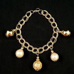 Bauble Charm Bracelet:Oh gold and pearls are just so Old Hollywood! This gold charm bracelet features silver and pearl bauble's on a 8 inch gold chain with a gold clasp closure. We love an elegant and versatile piece that can be dressed up or down! This charm bracelet is a vintage dead stock, brand new and never been worn. $16.00
