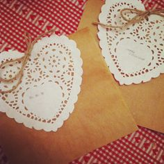 Homemade gift bags made out of brown sandwich bags, doily and string.