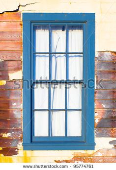 Distressed Exterior Wooden Window Painted Blue In A Wall Of Broken Stucco