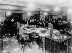 A group of unknown men gathering in The New York Times newsroom following the R.M.S. Titanic sinking, 1912.