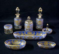 Art glass 8-piece Dresser Set, consisting of 2 perfumes, 2 boxes, ring stand, and 3 bowls, all with blue flash and gilt floral decoration.