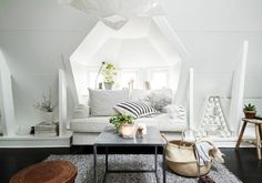 In this all white living room, black hardwood floors, striped throw pillows, house plants, and textured area rug stand out. Wooden furnishings and woven basket add warmth.