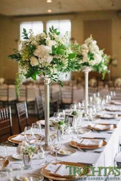 Tall elegant table centerpieces that have white flowers, but have black vases.